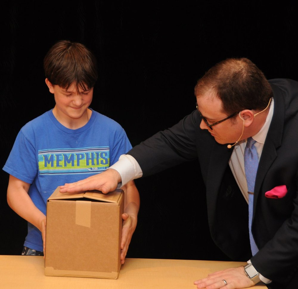 To demonstrate how bullying victims can feel, a student is suddenly unable to lift a small cardboard box.