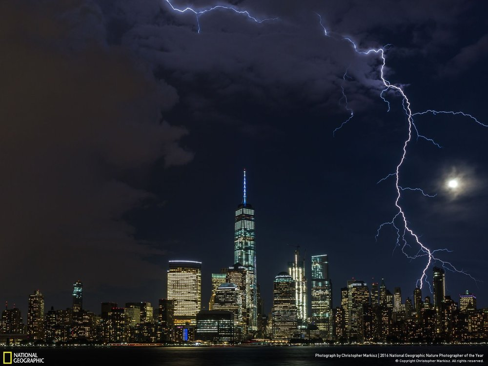 Moonlighting by Christopher Markisz: Lightning strikes lower Manhattan as a summer storm approaches a moonlit New York City skyline. Location: United States