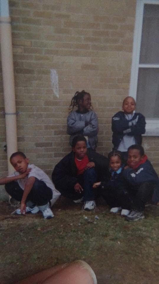 JayQuan is pictured in the center (third person going left to right) wearing a jacket and rocking braids.