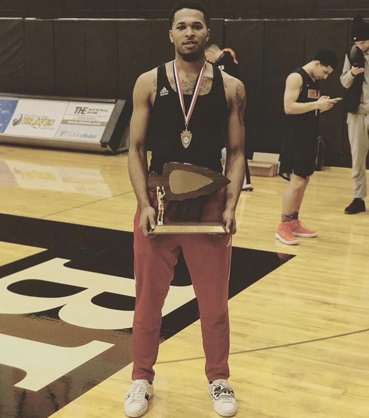 JayQuan holding the district title championship trophy during his time at Highland Community College.