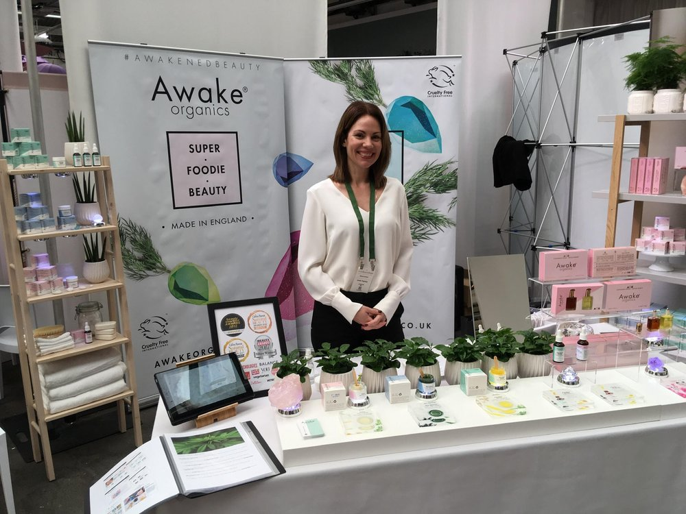 Melissa,  Awake Organics ' founder, alongside her stand and organic product range.