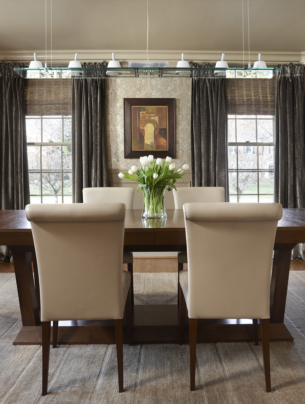 "The goal in this dining room was to give a nod to the couples' modern aesthetic while maintaining the architectural flow from outside this Colonial home. Our concept was that a young couple had inherited a Venetian palazzo. First, we raised the chair rail, and added some panel molding, then we applied a vintage looking damask wallcovering to add instant ""age."" Dramatic green silk vintage linen velvet drapery and grass shades add texture. In the center of it all, contemporary Italian furniture and lighting contrast, yet compliment, the rest of the room. Photo by Beth Singer."