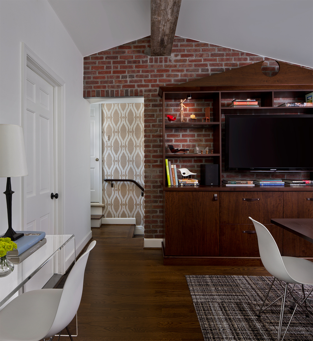 Layers of materials: A reclaimed barnwood beam, brick , walnut wood and patterned carpet and wallcovering add warmth.