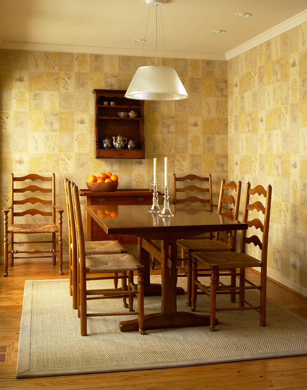 This breakfast nook is a study in simplicity, and how traditional and contemporary relate. Our clients loved their shaker table and chairs, and were thrilled when we said they worked in the new design. This room sits adjacent to the garden, so we had the walls covered in a block-printed botanical pattern, and then hung the very contemporary glass light over the table. The look is warm, traditional, and modern at the same time. Photo by Beth Singer.