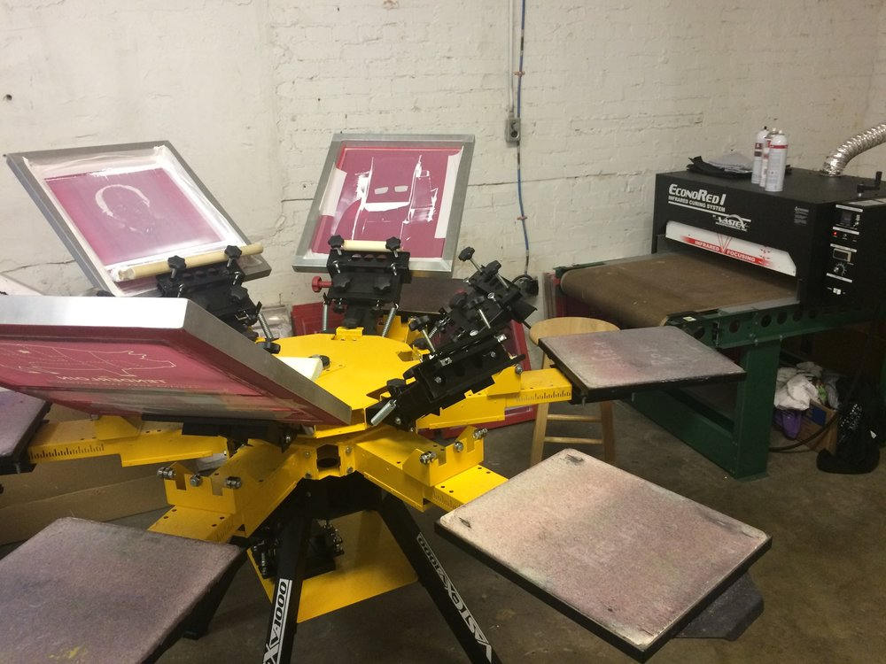 Our screen printing press has 6 arms. Right now, it has 4 pallets loaded on it. For shirts with multiple colors, one color of the design will be loaded on each pallet.