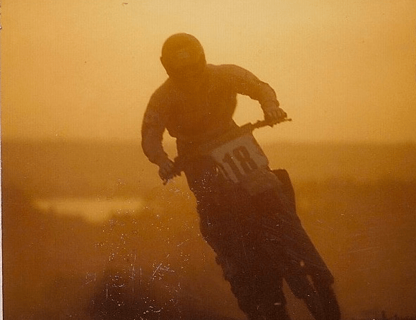 Christian coming out of the dust enduro racing in France on his Kawasaki KX250 early in the morning