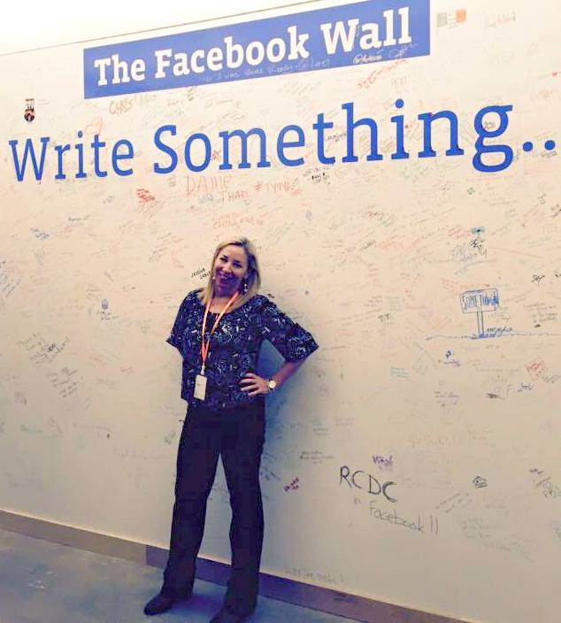 Sande Snead poses in front of the real Facebook wall at their offices.