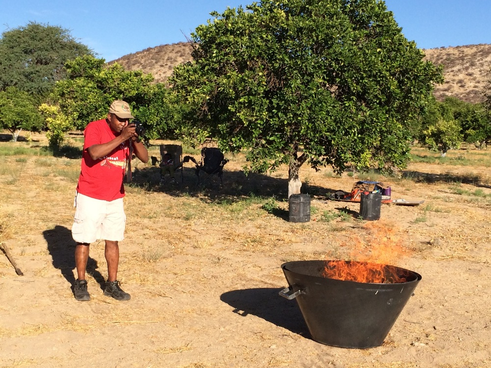 Dr Simon Angombe photographing the Kon Tiki kiln making biochar with invasive bush wood. Note no smoke.