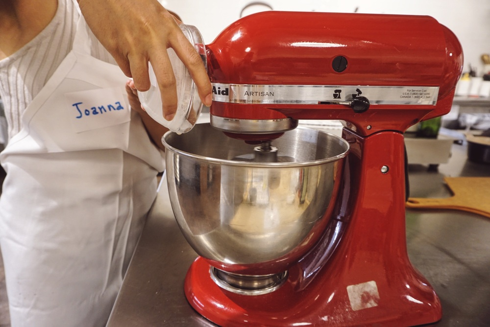 Using the kitchenaid to make our pizza dough, pouring the dry ingredients first.