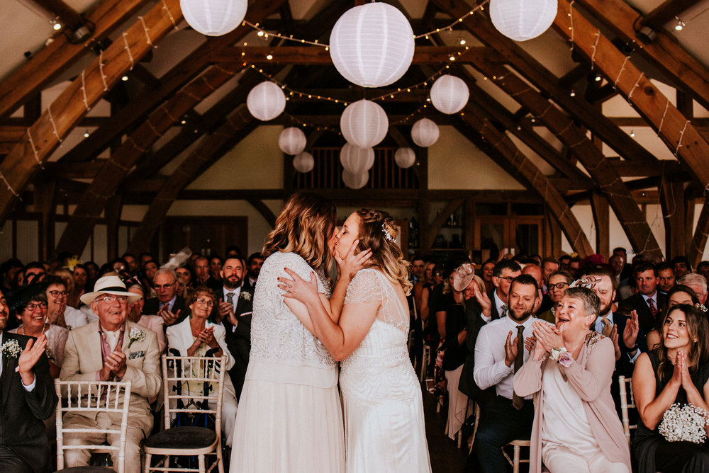 A tale of two brides in the beautiful wooden beamed barn venue of Sandburn Hall. Golf club portraits, Fairy lit first dances & a love without compare for Kaity & Charlotte's York wedding.