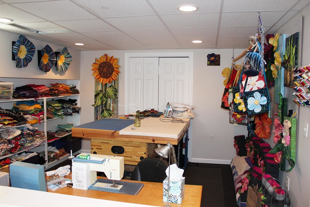 Clean studio. Fabric on the left, happy art all over the place, and my old tiny machine in front. (My kids will use the old machine and my new machine will be to the right of them (to the left in this photo.)