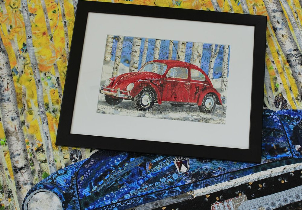 "Fabric quilt in the background and a framed 8"" x 12"" metallic paper print of ""1964 VW bug with Winter Birch"" in the foreground."