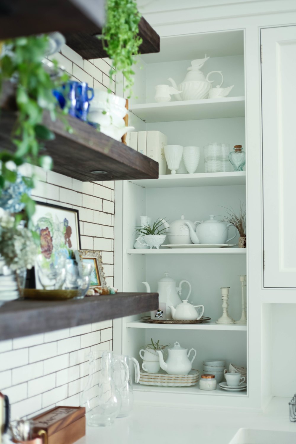 "Style tip: Display various white accessories, here I show off my white tea pots, candle sticks, vases, bowls, cups and books. I also added some air plants for pops of green.  Think ""white on white""  Style tip: You want shelves to feel loaded and bountiful and still looked stocked even with items in the dishwasher."