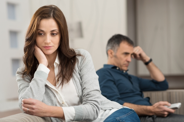 image of worried looking couple sat together on sofa