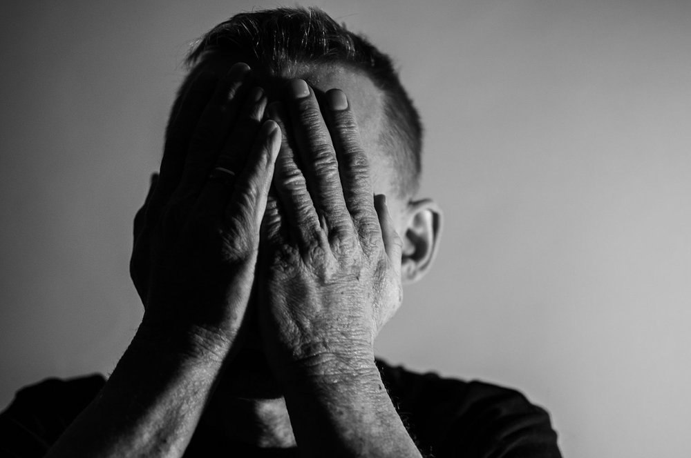 image of man with face in hands representing depression