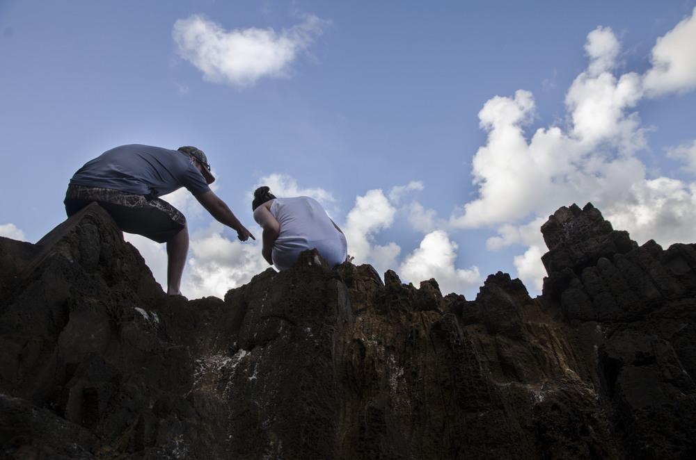 Tourists climb rock formations on Meagan's Bay, U.S. Virgin Islands