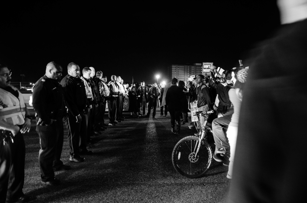 A line of police officers and protesters face each other in downtown Dallas on November 25, 2014.