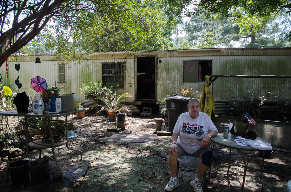 Diane Andrews sits in front of her Baton Rouge home after the flood.