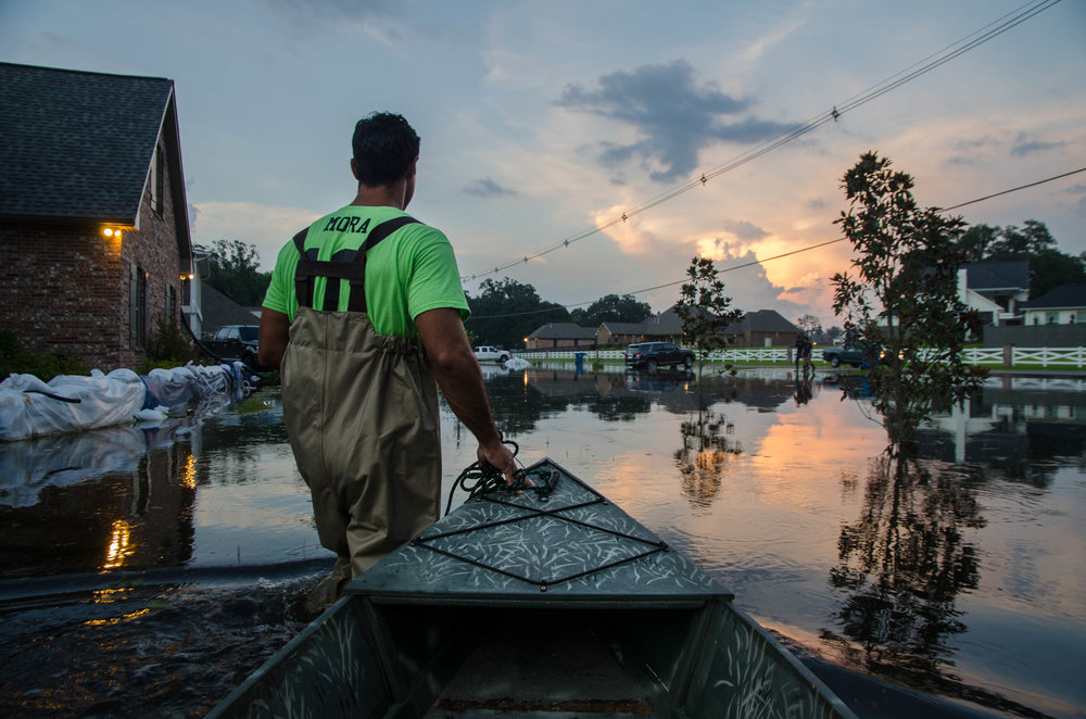 Blake Mora checks on the sand bags protecting his house on Bluff Rd in Baton Rouge, Louisiana.