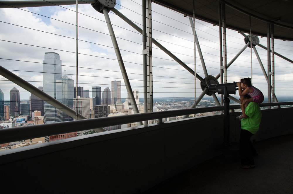 A young girl sits on her mother's shoulders to look at the view from Reunion Tower in Dallas, Texas.