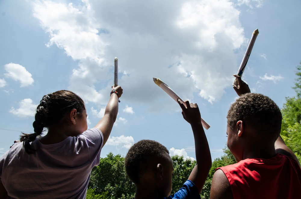 Young children imagine how high their paper rockets will go at the Perot Museum in Dallas, Texas.