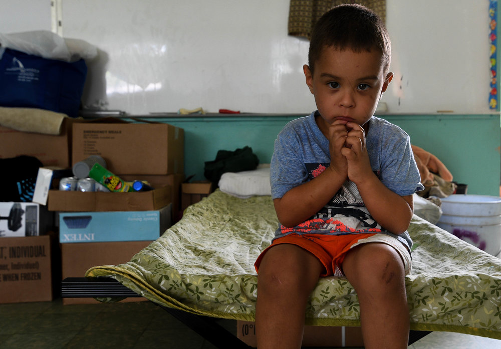 """EXPAND   Five-year-old Jeyden Quinones isn't used to the food the military has given him. He wants plantains, his favorite food. Over the past few months, he and eight family members have been sharing one room and four beds in the cramped Jayuya school shelter that remains without power. Although they're strapped for cash, his family used the last of its money to buy a small stove so that Jeyden can once again eat plantains. It's the last thing left of home for him, his mother says. """"The wind took my house,"""" the boy says. """"The hurricane made my house explode. I only have hope in God now."""""""