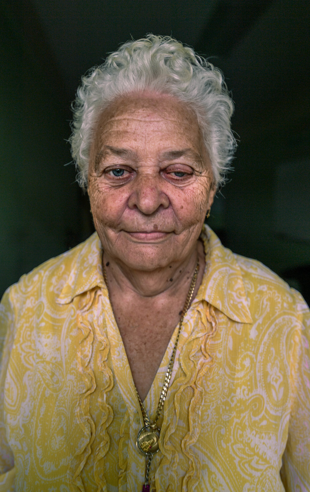 """Josefina Adonte, 71, stands in her room at the Adjuntas shelter. Before the storm, Adonte was living in assisted care. Now, she struggles to take care of herself in the shelter with no nurse. Because of glaucoma and dementia, Adonte cannot complete daily tasks, like taking herself to the bathroom at night. """"No one is there for me, so I just lay there,"""" Adonte said. The Adjuntas shelter plans to close soon, leaving many of its residents homeless. """"I don't know where I'll go,"""" Adonte said. """"If I am alone, I will die."""""""