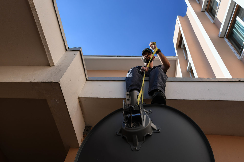 After internet is restored at a Quebrada Grande Hospital, Darrick Kouns, a volunteer for ITDRC, lowers a dish from the roof to relocate it to a shelter in need.