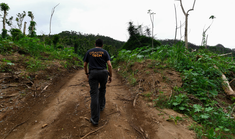 Darrick Kouns walks down the mountain roads of Dominguito, Puerto Rico, attempting to navigate around a downed bridge. Damaged or destroyed mountain bridges leave some locals traveling by four-wheelers or dirt bikes. Remote villages in Puerto Rico, like Domingutio, Maricao and San Lorenzo, have been isolated since the storm destroyed bridges that connect them to bigger cities. ITDRC visited the remote mountain villages, helping some get back online and noting those without power so they can revisit.