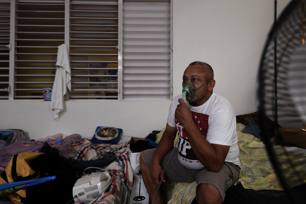 Alfredo Matos Rivera, 58, sits on the edge of his cot next to other displaced families while focusing on his breathing treatement. Matos has been in the shelter outside of Dominguito for more than 72 days. Hospitals in his area remain without power, and with the loss of his house, job and car, traveling to a hospital in his area is not an option.