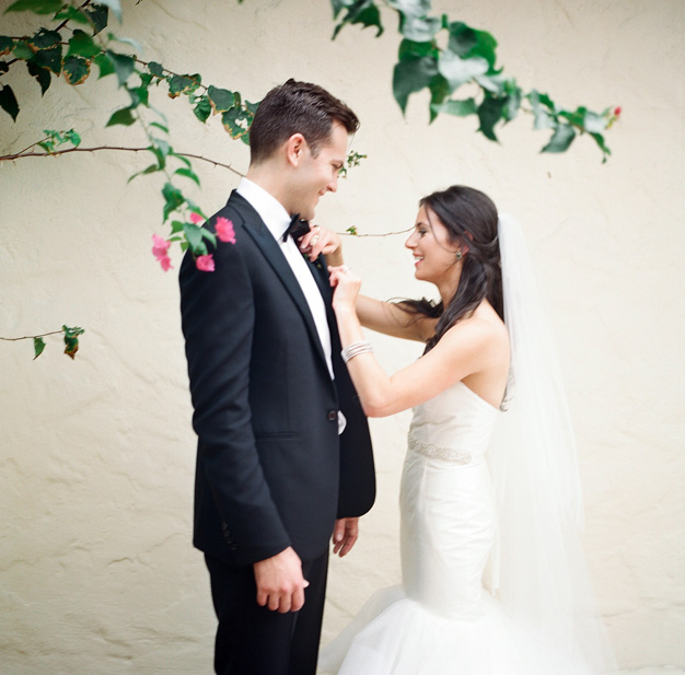 Bride pins boutonniere on groom - photo by Kat Braman