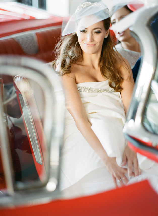 Bride heading to Palm Beach Wedding in red vintage convertible - photo by Kat Braman
