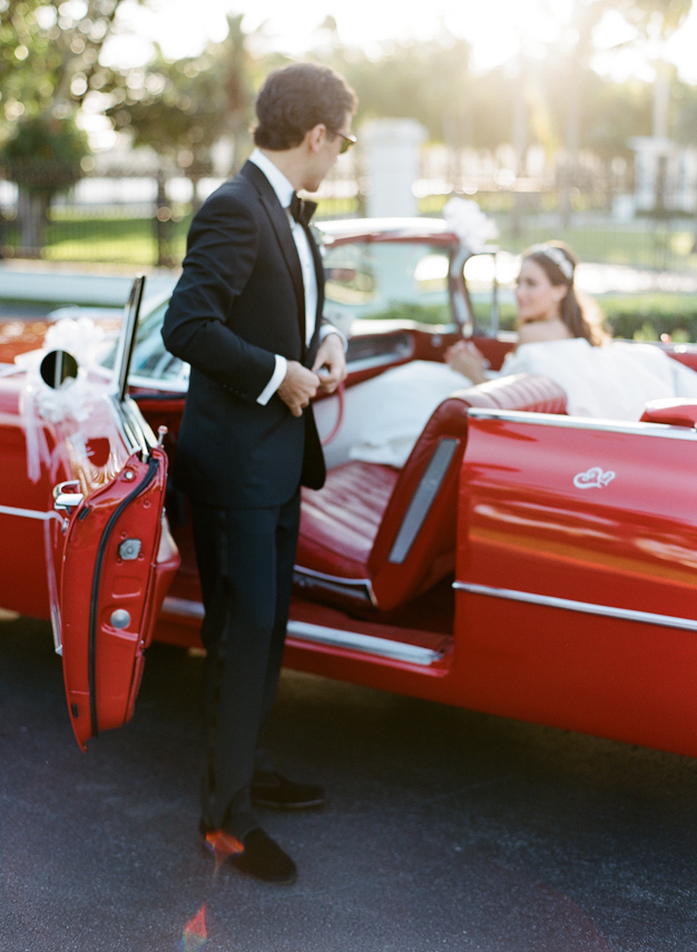 Bride and Groom arriving at Flagler Museum in vintage red convertible - photo by Kat Braman