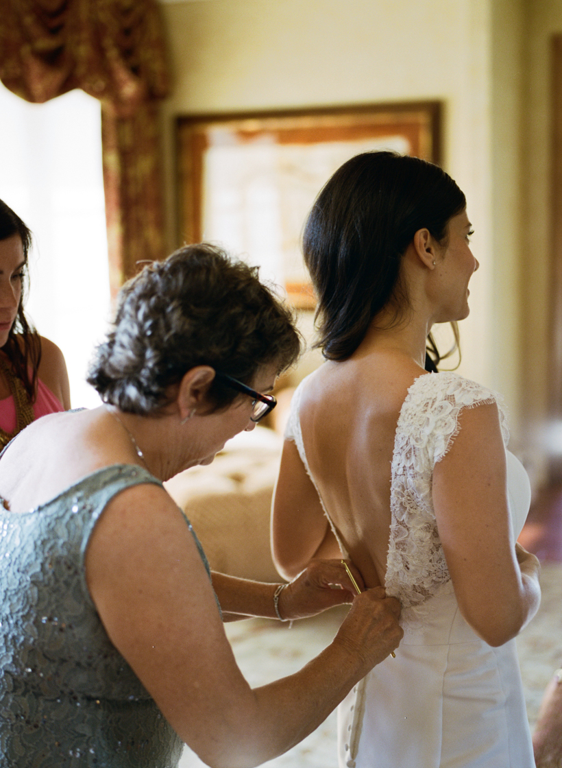 Mother of the Bride helping with the buttons on this one of a kind lace dress - photo by Kat Braman
