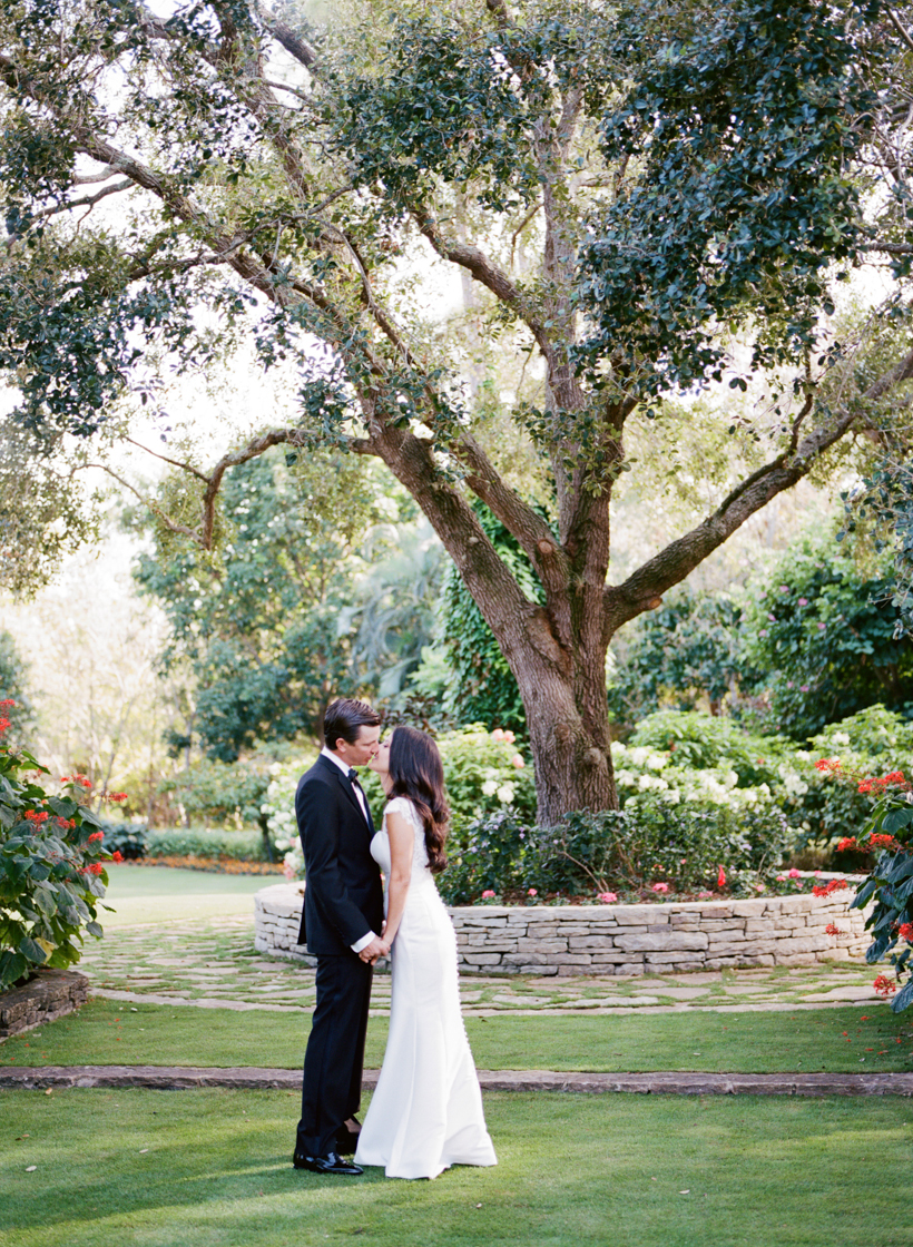 Bride and Groom in a beautiful garden setting in Palm Beach - photo by Kat Braman