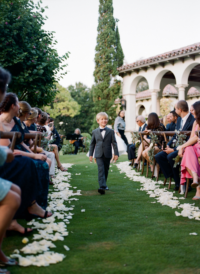 Handsome ring bearer walks down the flower-lined aisle.  Photo by Kat Braman