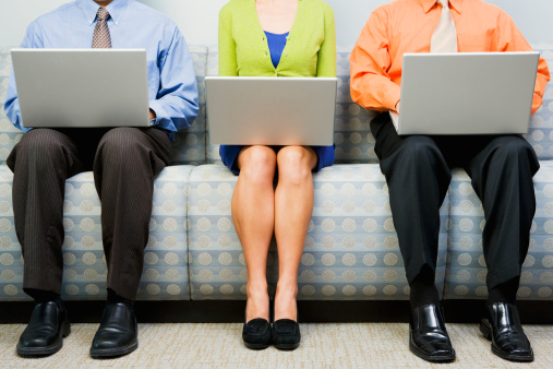 three people on laptops