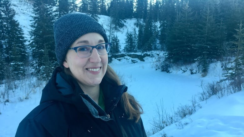Rebecca Ellis, conservation manager with the Edmonton and Area Land Trust, surveys Larch Sanctuary, discovering tracks in the snow left by deer, mice and muskrats. (Adrienne Lamb/CBC)