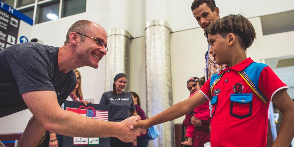 World Relief Atlanta Office Director Joshua Sieweke welcomes Malik, a 9-year old Syrian refugee, at Hartsfield–Jackson Atlanta International Airport.