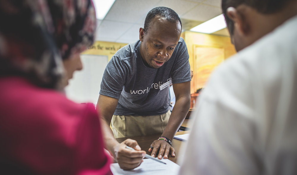 Gicheru Njoroge, Case Specialist at World Relief's Atlanta office, assists a recently arrived refugee family from Syria.