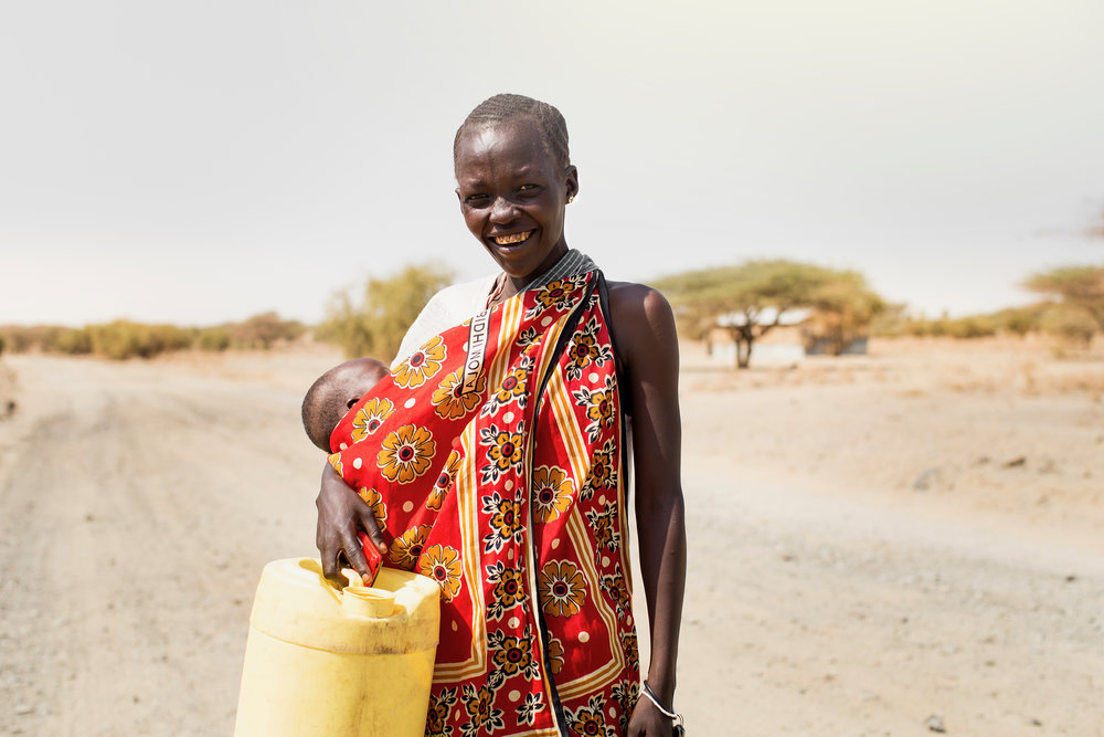 A mother and her infant child retrieve water from a well in her village built by World Relief and its partners.  [Photo courtesy  GI-INC ]