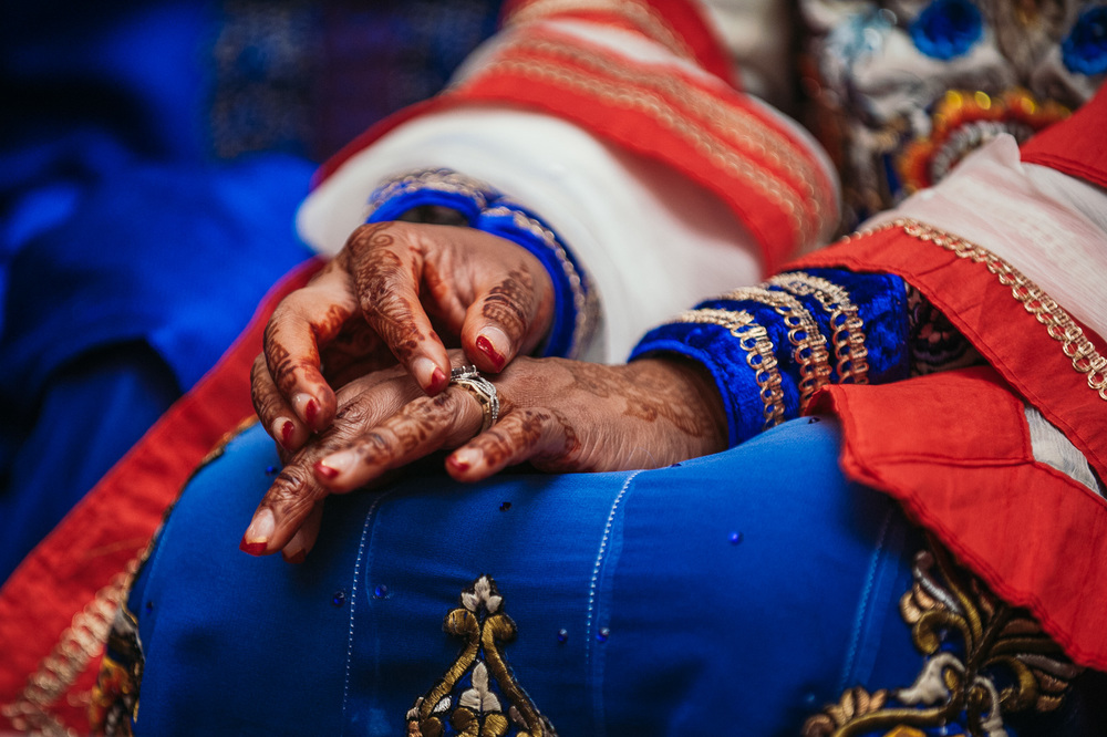 "^""Love is colourful thing.""   Ramiza and Aaron's dual wedding ceremony was a huge highlight for me.  Their Indian ceremony was rich with every colour in the spectrum, alive with dancing, and rich with blessing.  It   looked   the way a heart feels when it's exclaiming love.  This simple shot of Ramiza aligning her rings during her Indian ceremony, really highlighted the vibrantly contrasting colours of her gown,  gold embroidered accents, and her intricate mehndi."