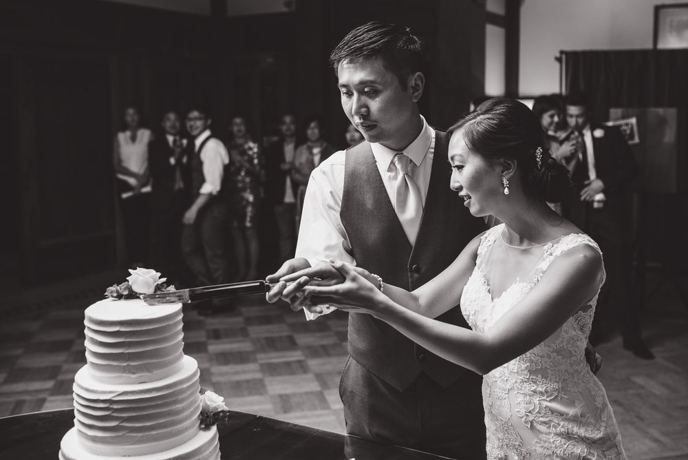 bride and groom cutting the cake at their wedding at cecil green park house on ubc campus in vancouver - victoria wedding photographers