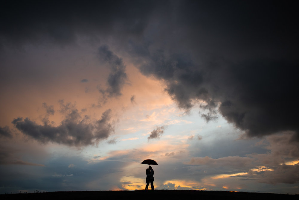 silhouette of a couple standing under an umbrella with a dramatic sky - victoria wedding photographers
