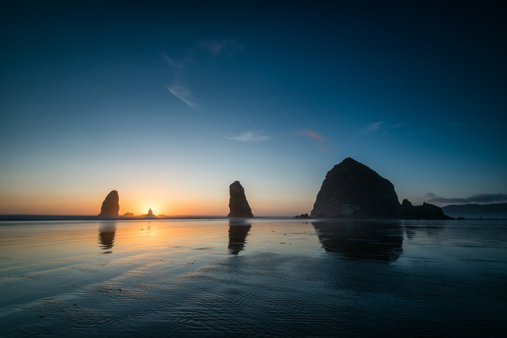 One of my shots of sunset as the sun disappears behind the smaller rock at Cannon Beach.