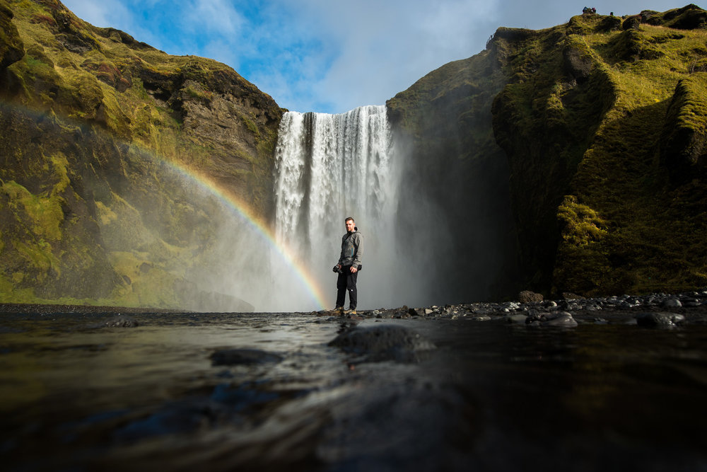 Matt at the end of a rainbow, at the bottom of Skogafoss.