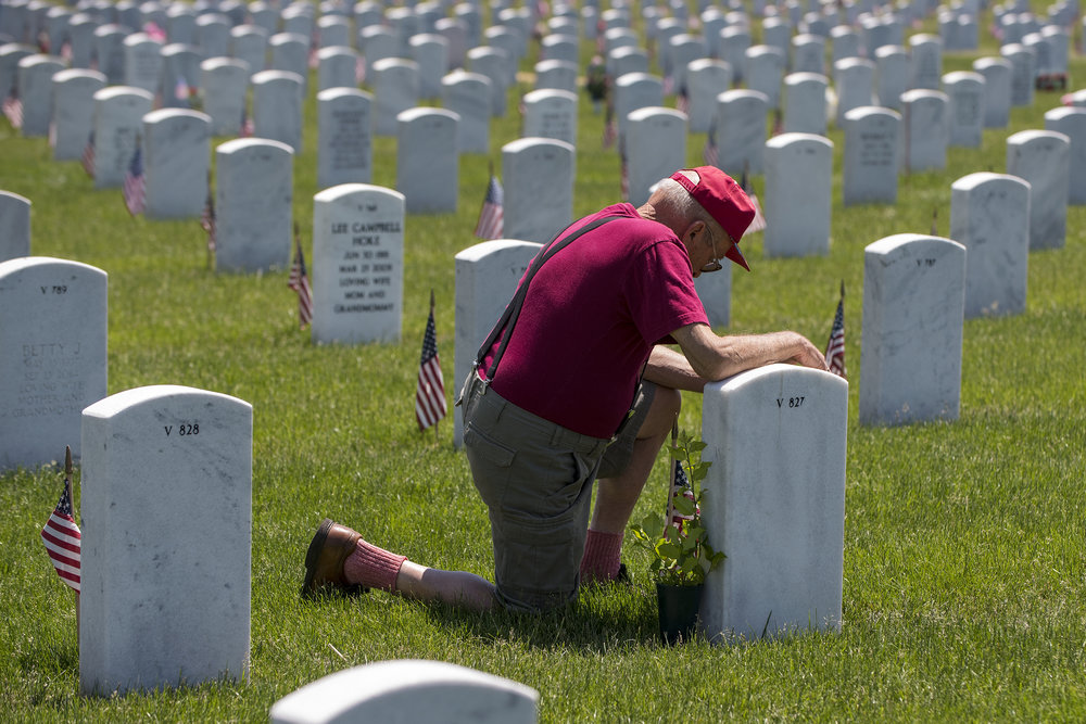 """You come to see your loved ones,"" Army veteran Nicholas Fotiadis of East Moline said after kneeling at the gravestone of his wife Mary Ann Fotiadis. ""I think what [Memorial Day] is supposed to stand for is the important thing. … If you served, I think you deserve this."" Fotiadis, whose father and brothers also served in the military, placed a yellow rose and an American holly at his wife's grave May 30 at Rock Island National Cemetery. — May 30, 2016, Rock Island Arsenal, Illinois."