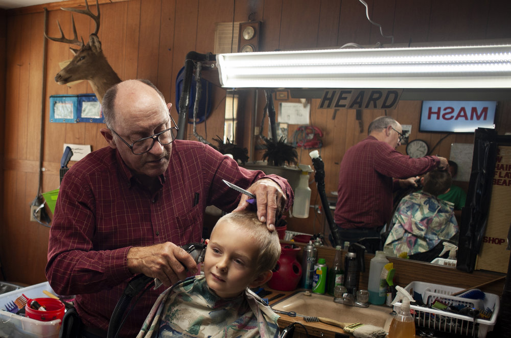 """Barber Terry Heard, of Hoxie, gives a haircut to Hunter Capps, 7, of Lynn, on Saturday, Oct. 20, 2018, at Whiteway Barber Shop in Walnut Ridge. Heard has been a barber in Lawrence County for nearly half a century. """"I never did think that I'd live to see that I had the only original barber shop in Lawrence County,"""" Heard said. Photos and story by Jacob Wiegand   The Sun"""