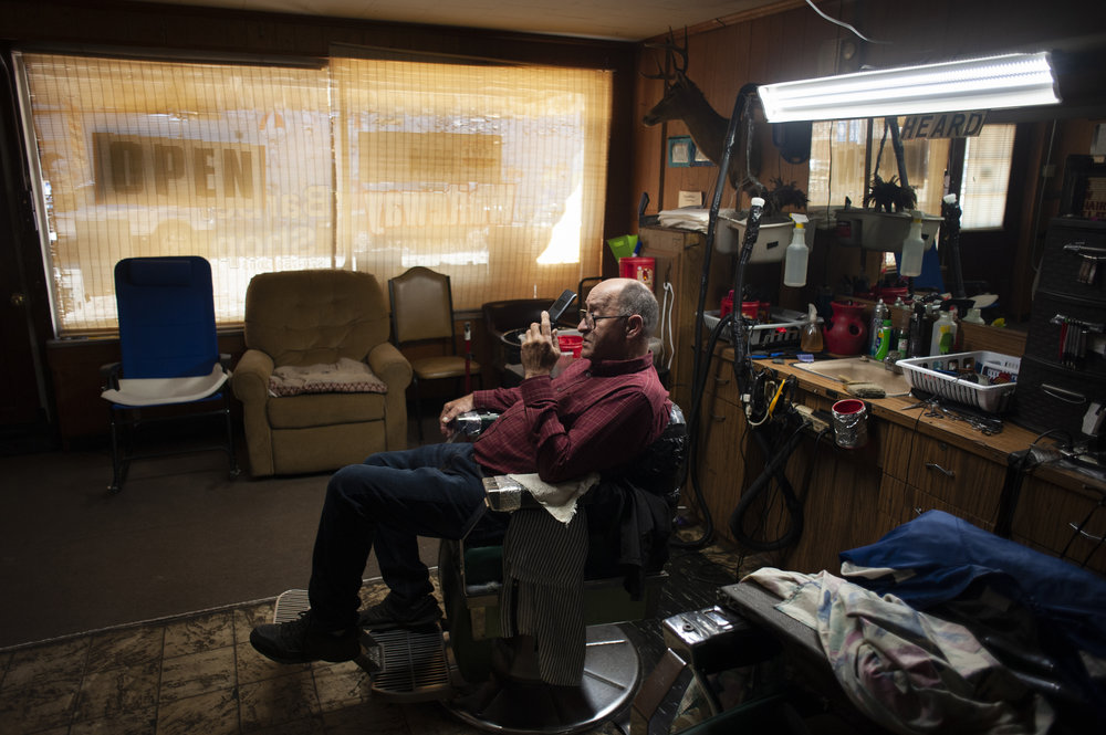 Following his last customer exiting his shop, Heard takes a load off in his barber chair to make a call Oct. 20 at Whiteway Barber Shop in Walnut Ridge.