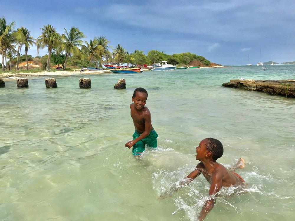 Kinder planschen am Strand von Union Island. (Foto: Holger Ort)